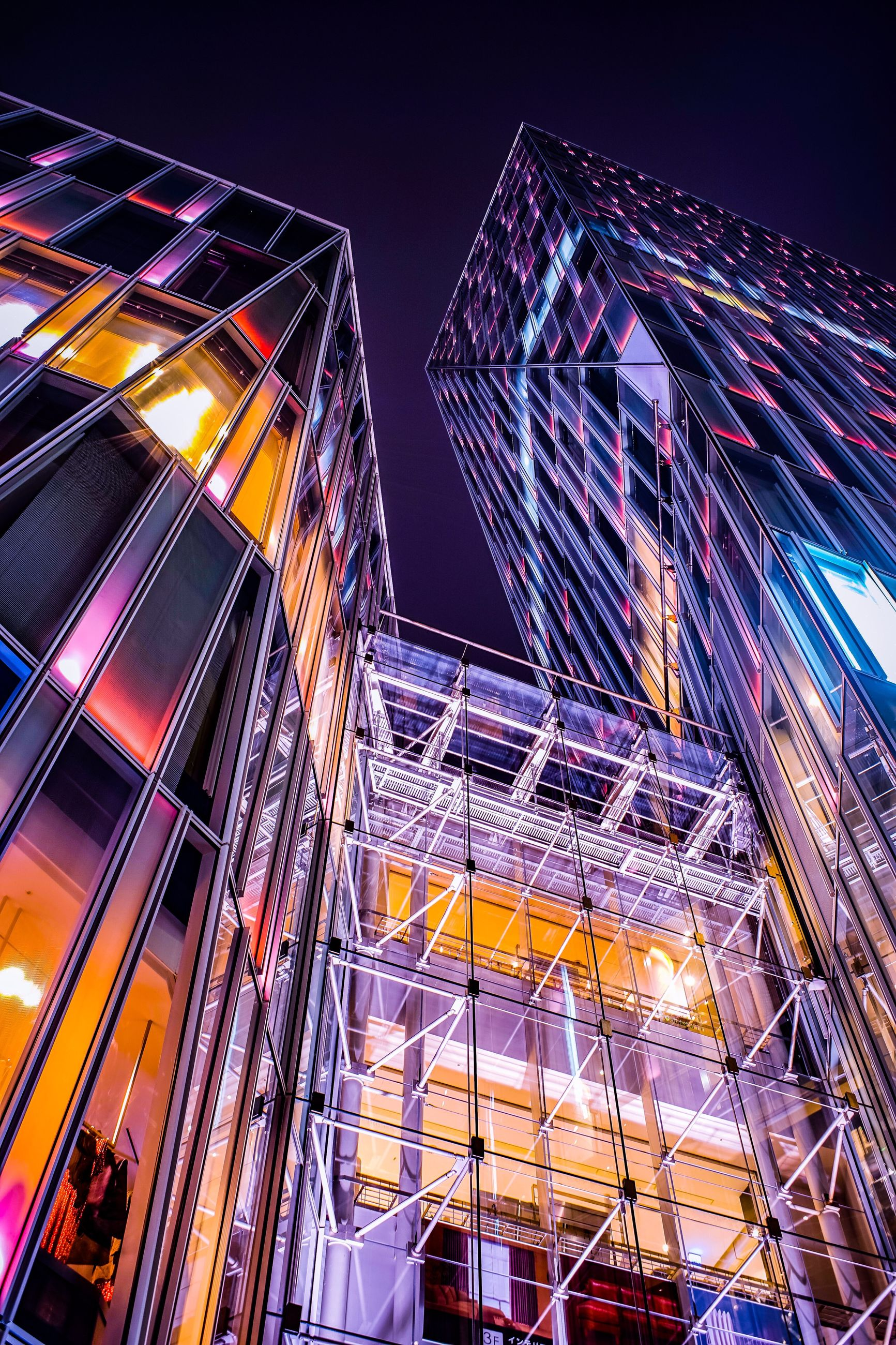 illuminated, building exterior, architecture, built structure, night, low angle view, city, sky, building, modern, office building exterior, tall - high, no people, glass - material, nature, office, outdoors, clear sky, skyscraper, multi colored