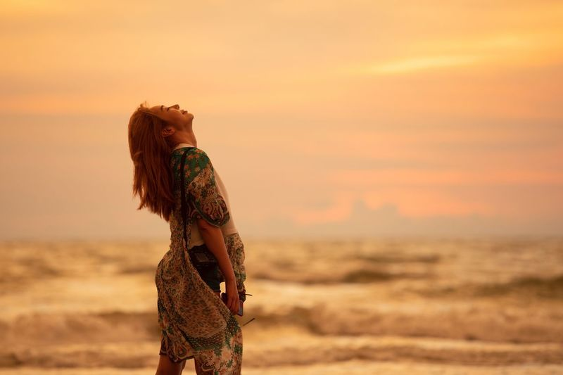 Side view of woman standing on beach during sunset