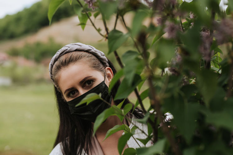 Woman with face mask looking behind the tree in nature