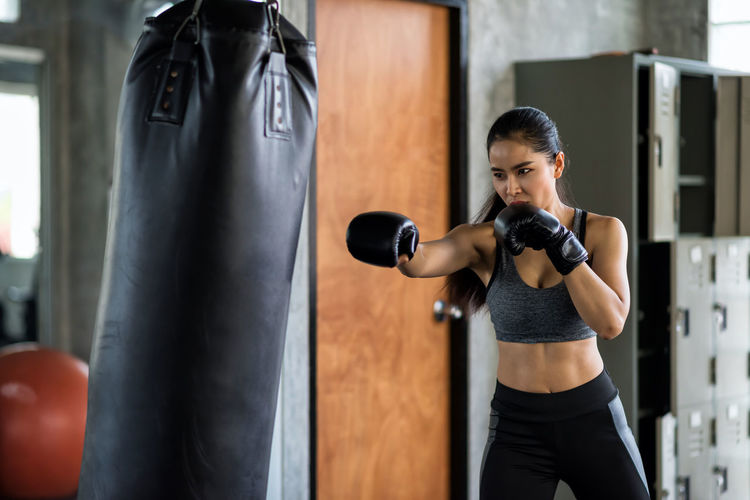 Beautiful woman practicing boxing in gym