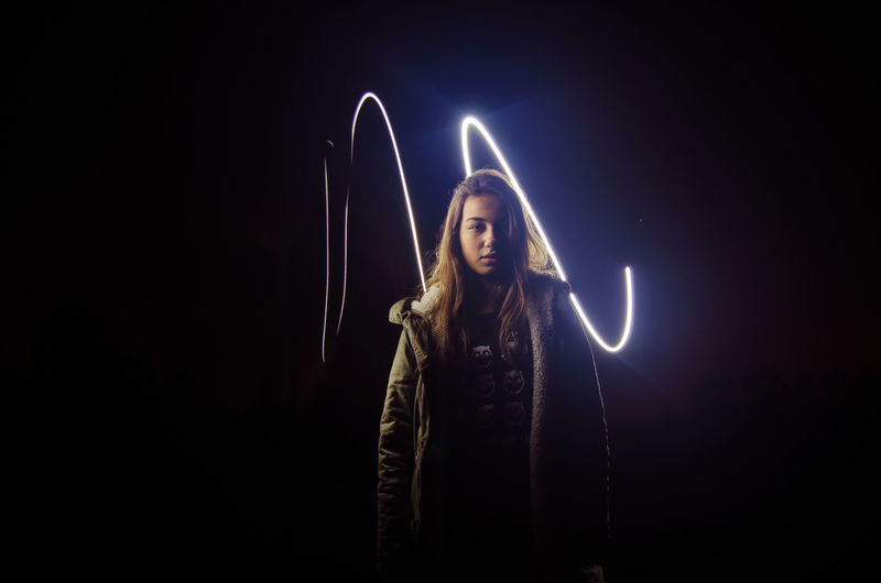 Portrait Of Young Woman Standing Against Light Painting At Night