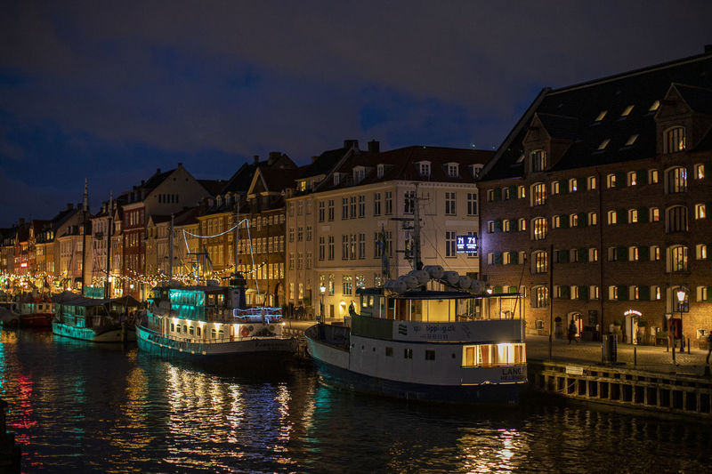 Boats in canal amidst buildings in city at night