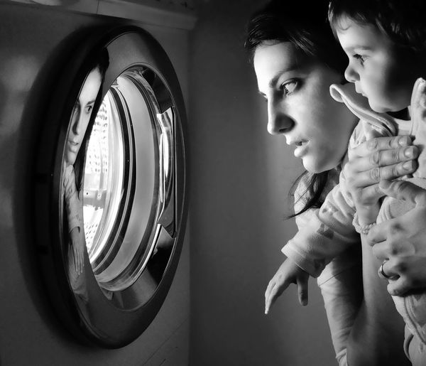 Side view of woman with boy looking at washing machine
