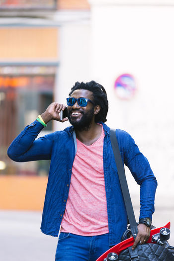 Young Man Walking While Talking On Smart Phone In City