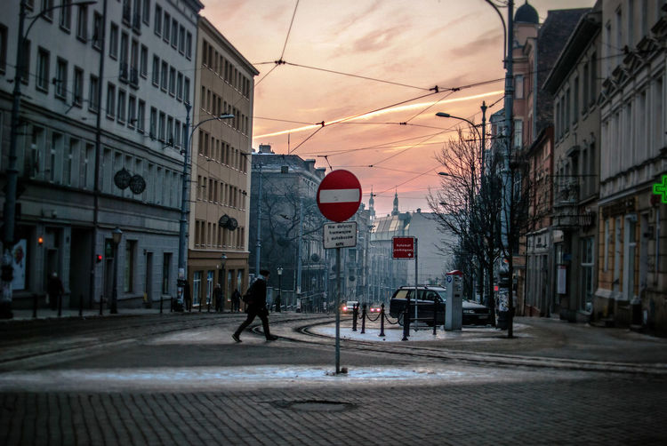 Side View Of Man Crossing Road In City During Sunset