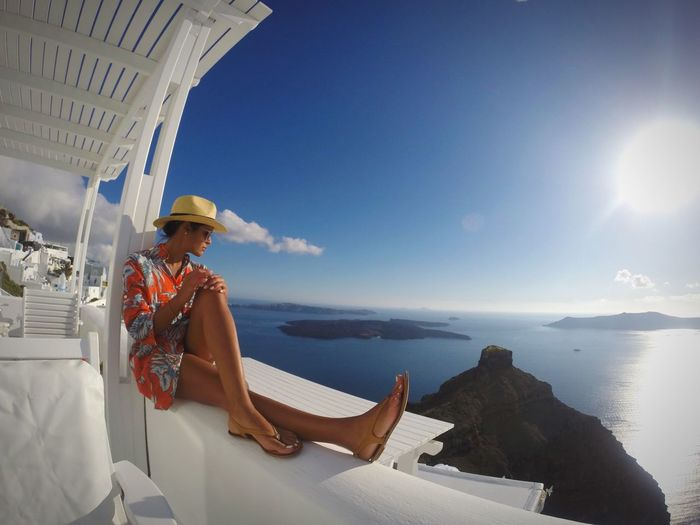 Woman Sitting On Railing At Santorini Against Sky