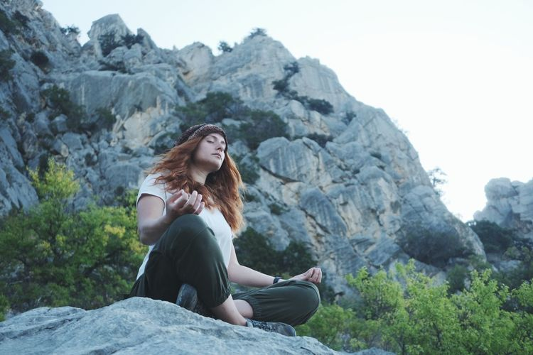 Low angle view of young woman meditating while sitting on rock