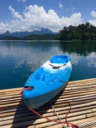 Blue kayak moored on wooden raft over lake