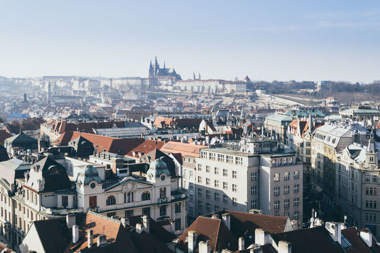 Cityscape of prague on a sunny and cold winter day with blue sky, castle in the background