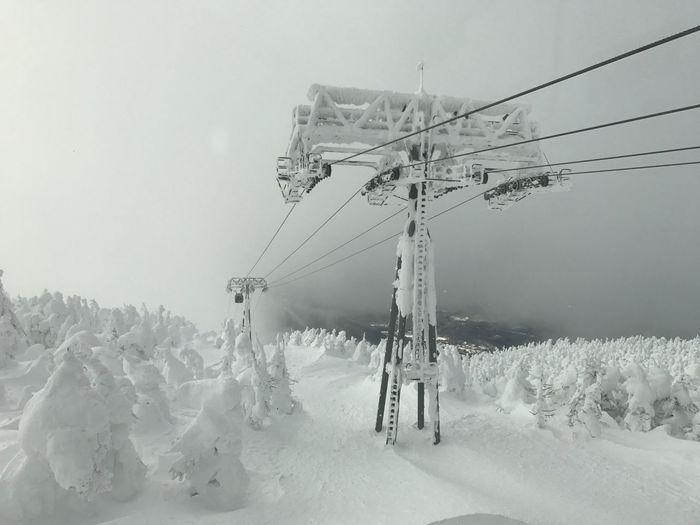 Ski lift on snow field against sky