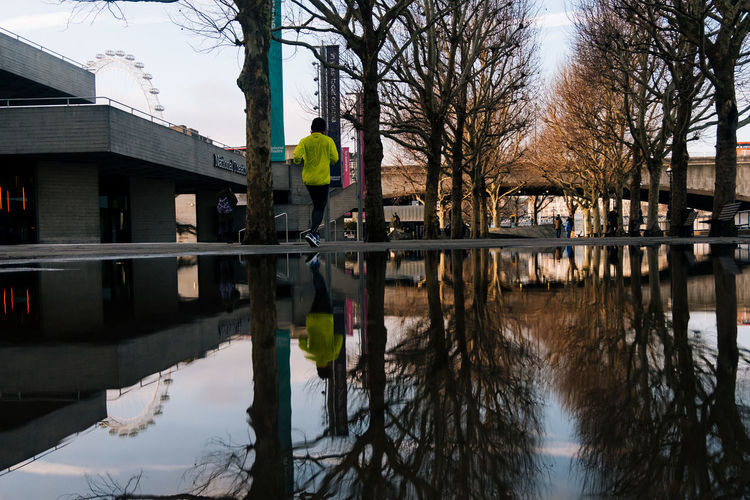 Way to go Outdoors Architecture Fujifilm_xseries Streetphotography Reflection Water Tree Built Structure Waterfront Puddle Nature Day One Person Real People Plant Standing Building Exterior Sky Lake Men
