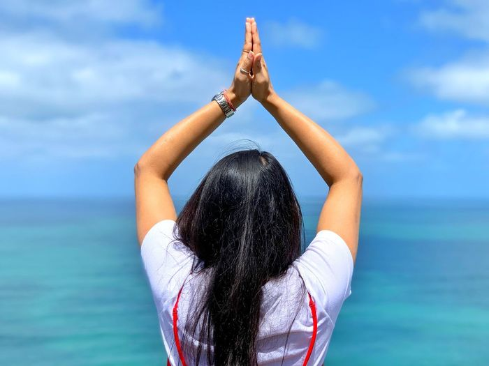 Rear View Of Woman With Arms Raised And Hands Clasped Standing By Sea Against Sky