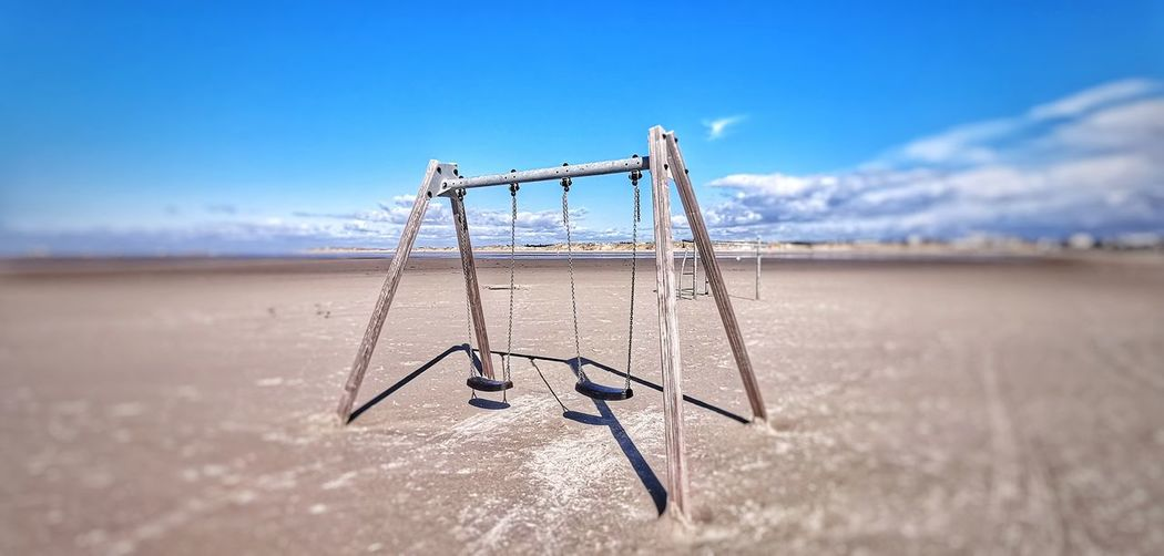 Sea And Sky Beach Photography Beach Day Wood Wood - Material No People Non-urban Scene Sky And Clouds Water Waterfront Blue Sky Blue Blue Color Childhood Beach Blue Sand Outdoor Play Equipment Playground Oil Pump Sky Swing Rope Swing Calm Countryside Horizon Over Water Ocean Sea Seascape Chain Swing Ride