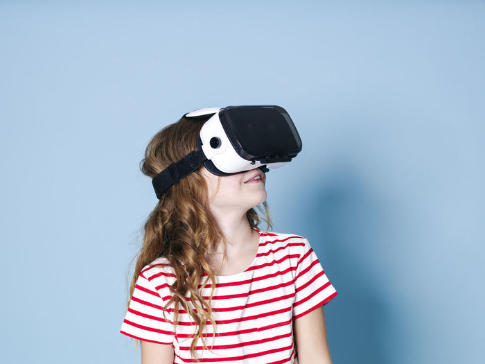 smiling positive girl wearing virtual reality glasses goggles headset, vr box. connection, modern, new generation, concept. girl trying to touch objects in virtual reality, studio shot on blue background Cyberspace Goggles Virtual Glasses Simulation Girl Entertainment Future Generation 360 3D Box Design Business Fun Joyful Gaming Game Electronic Futuristic Blue Copy Space Experience Young Human Woman Model Visual Viewer Video Film Look Observe Learn Pupil School Funny Technology Technical University  Visions Safety Glasses Glass Cool Female One Translated With Www.DeepL.com/Translator Striped One Person Leisure Activity Front View Childhood Women Child Portrait Headshot Fashion Casual Clothing Hairstyle Sunglasses Waist Up Girls Lifestyles Real People 3-d Glasses Blue Background Innocence