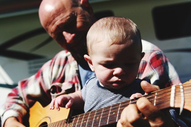 Midsection Of Man Playing Guitar With Child