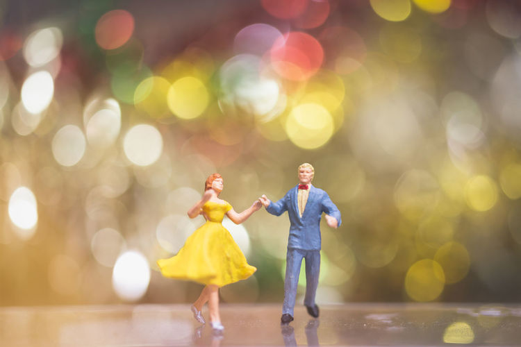Close-Up Of Dancing Figurines On Table Against Lights
