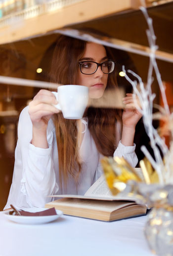 Close-Up Of Teenager Holding Coffee Cup While Sitting In Restaurant