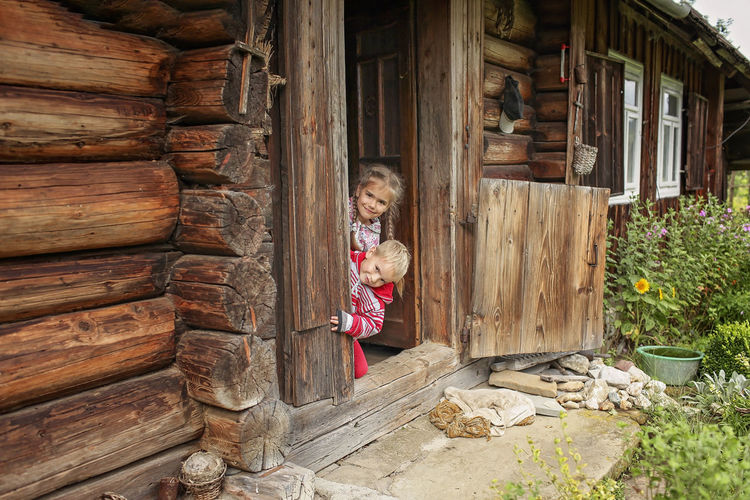 High angle view of girl standing by wooden hut