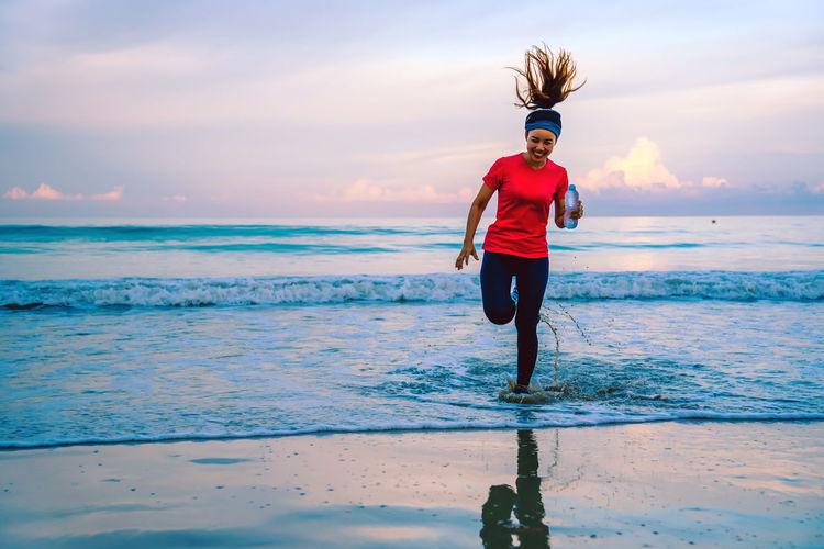 Woman holding bottle running on beach against sky