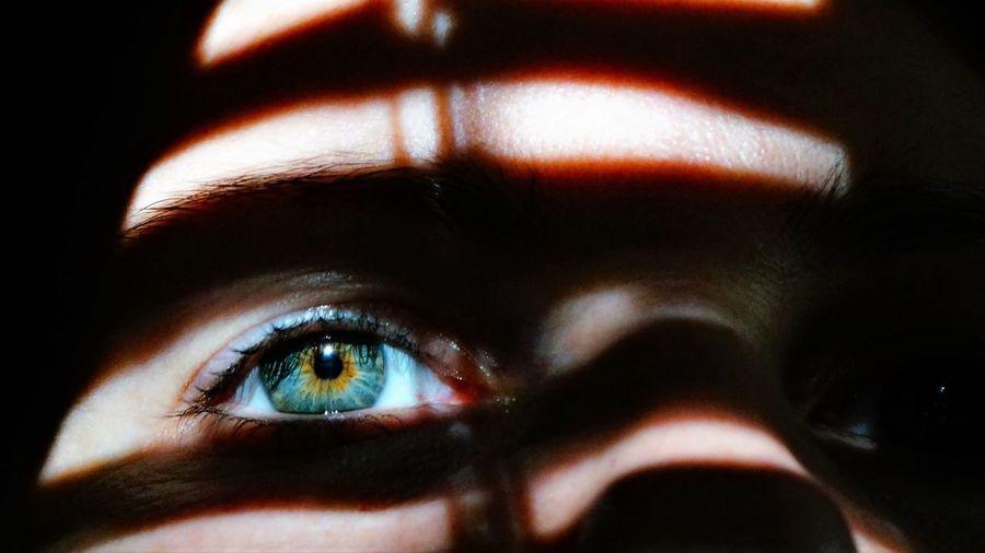Sunlight falling on woman eye in darkroom