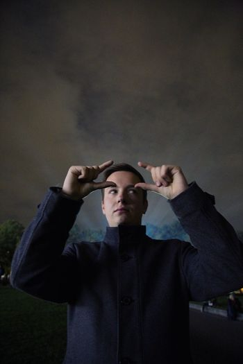 Thoughtful man gesturing against cloudy sky at night