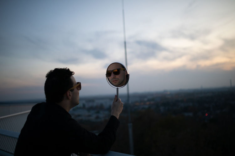 Side view of man holding mirror with his reflection against sky during sunset