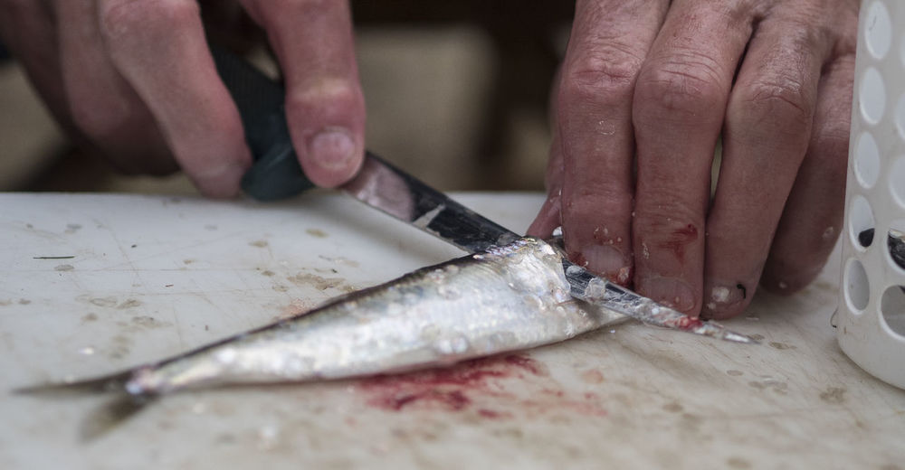 Midsection of person holding fish on cutting board