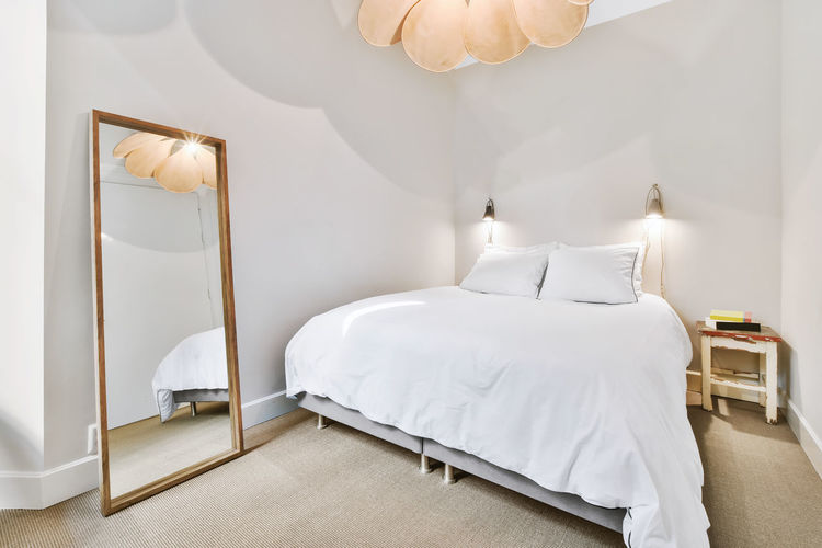 White image of empty bed in bedroom