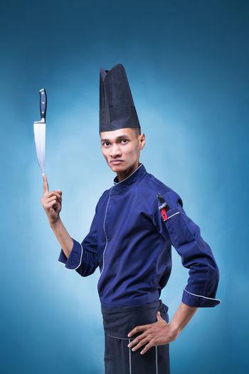 Portrait of chef balancing knife on finger against blue background