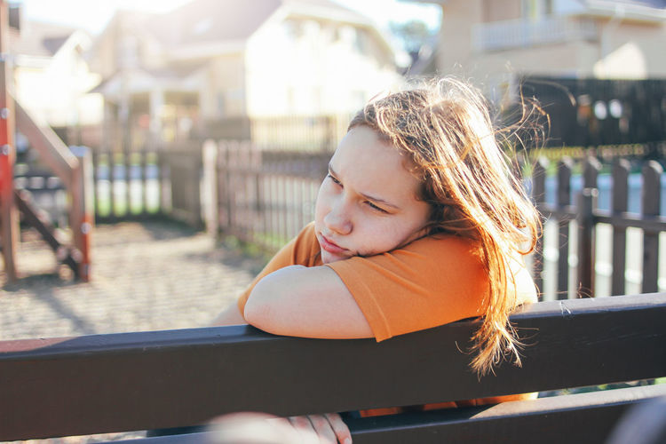 Thoughtful girl sitting on park bench