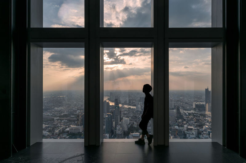 Silhouette man standing by window against cityscape