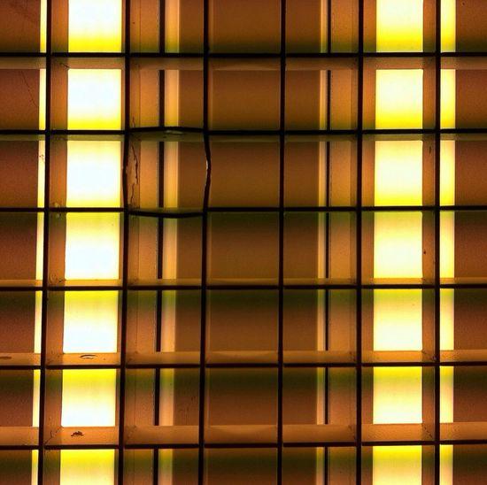 Directly below shot of illuminated fluorescent light seen through metal grate