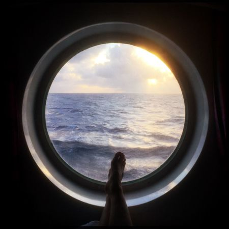 Onboard a cruise to Cuba in a room with a view. Ocean View Ocean Legs Feet Relaxing Relax Vacations Vacation Stateroom Cabin Porthole Cruise Cloud - Sky Sky Sea Horizon Over Water Nature Circle Sunset Water Beauty In Nature One Person Real People Scenics Window Close-up Tranquility Day