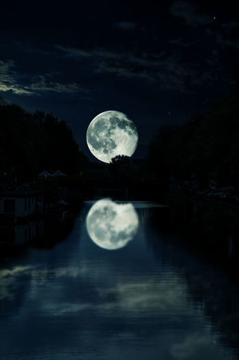 Scenic view of moon in river against sky at night