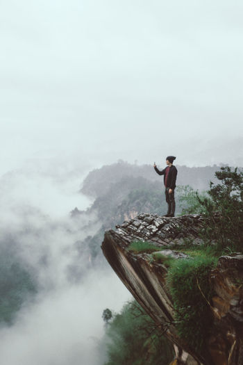 Man standing on mountain against sky during foggy weather