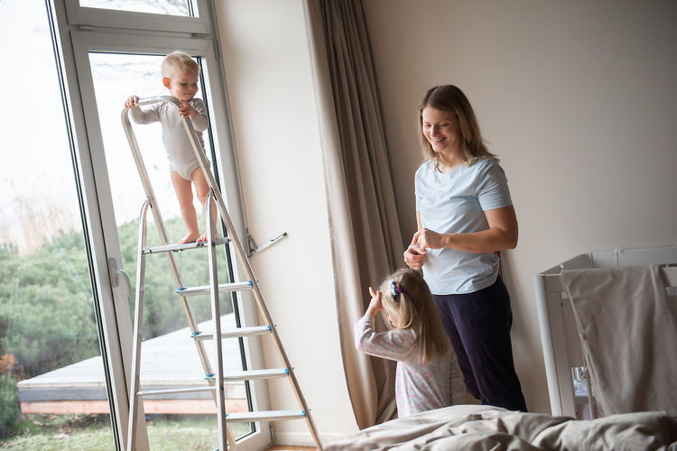 Woman standing with children in bedroom at home