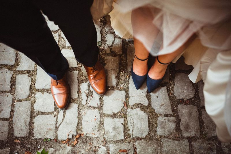 Low section of bride and groom standing on footpath