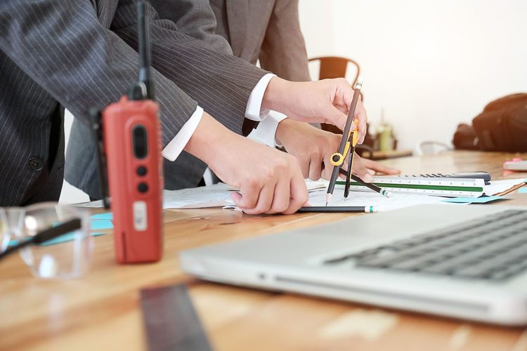 Midsection of business colleagues working on table