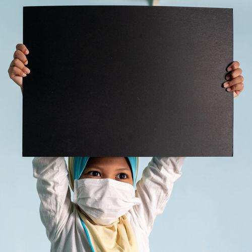 Portrait of boy holding camera over white background