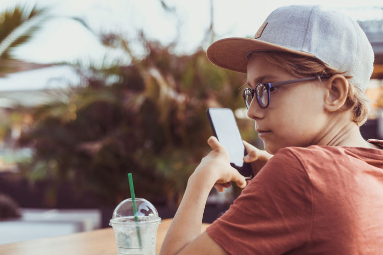 Boy using mobile phone while holding sitting outdoors