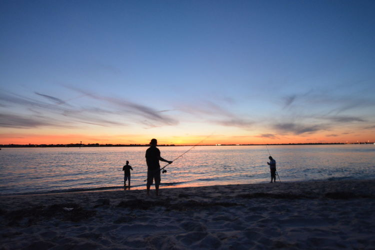 Silhouette men fishing in sea at beach against sky during sunset