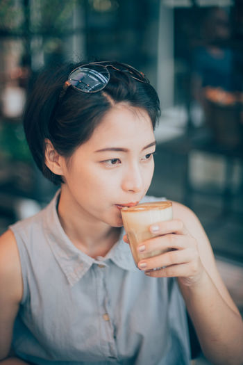 Close-up of young woman drinking drink in cafe