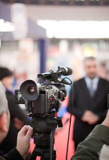 Man filming businessmen through video camera at event