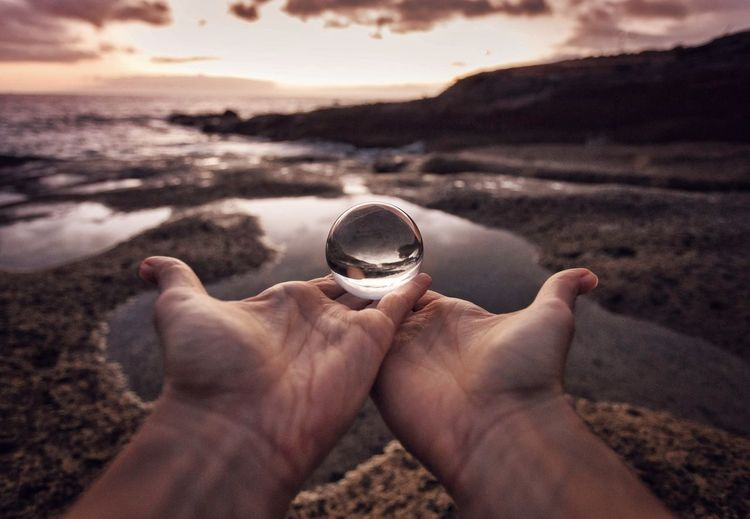 Cropped hands holding crystal ball at beach