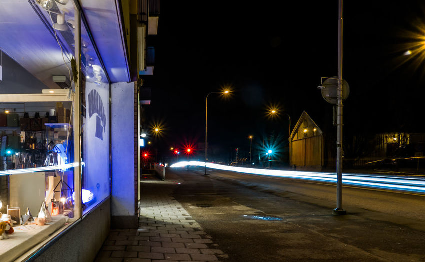 Illuminated light trails on road in city at night