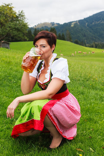 Portrait Of Mid Adult Woman Drinking Beer While Crouching On Grassy Field