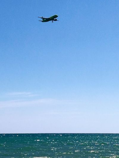 Airplane flying over sea against clear blue sky