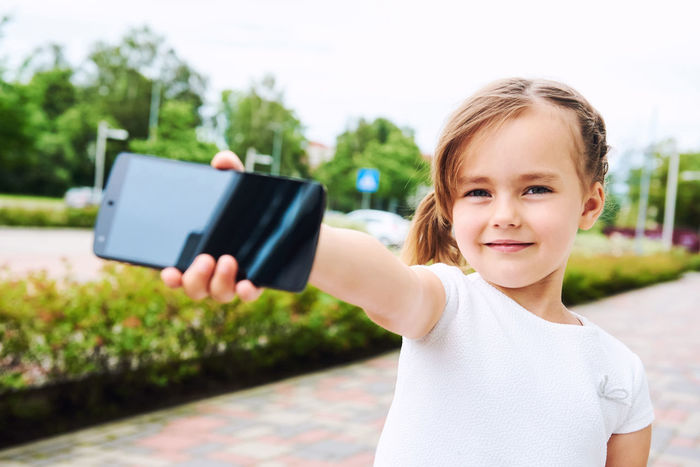 Adorable little girl with a smartphone outdoors. 5 Years Old Alone Beautiful Caucasian Cell Cellphone Child Daughter Device Entertainment Face Gaming Hand Holding Internet Little Girl Mobile Phone Outdoors Phone Player Small Girl Smartphone Street Summer Technology