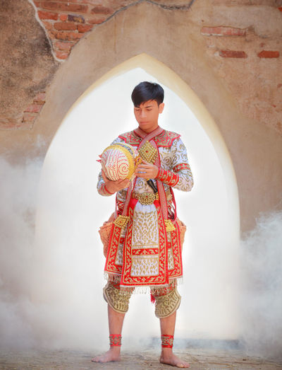 Full Length Of Man Wearing Traditional Clothing While Standing Against Building