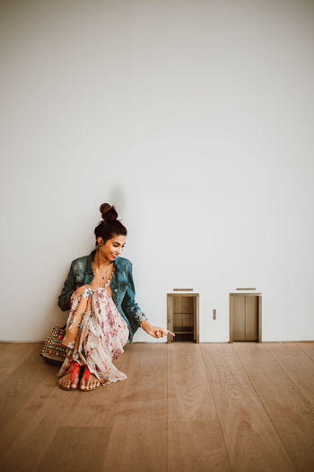 Woman sitting on hardwood floor against wall